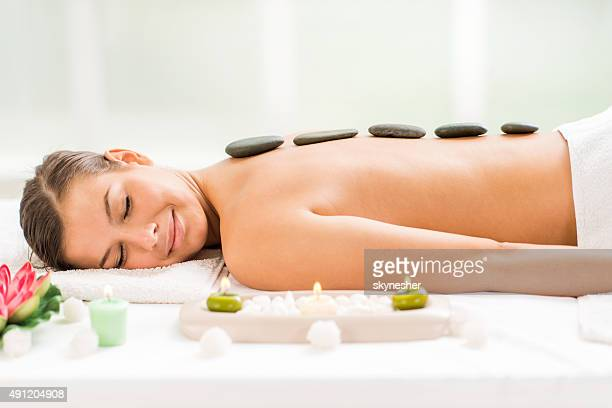 Young woman receiving stone therapy treatment.