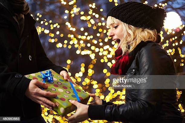 Young woman receiving xmas gift on city street
