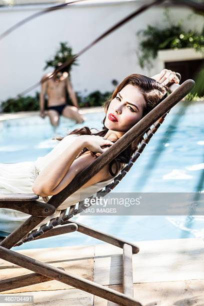Young woman reclining in sunlounger at poolside