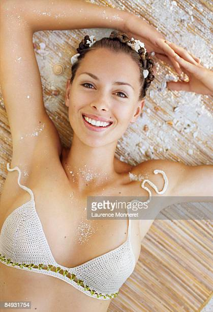 Young woman reclining on straw mattress and sand