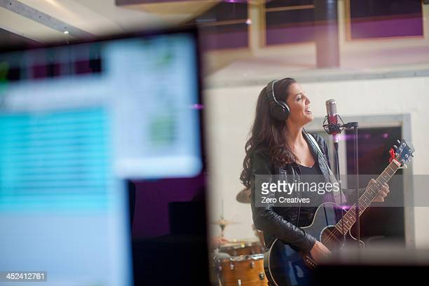 Young woman recording in studio