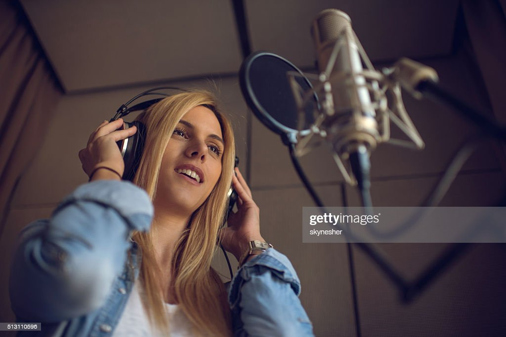 Young woman recording new song in music studio.
