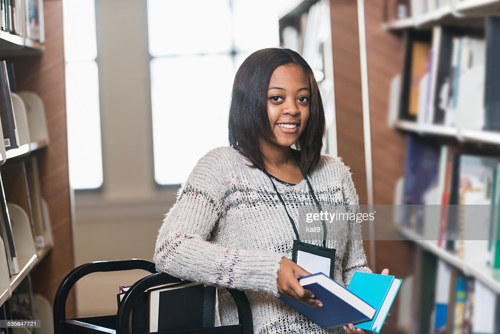Young woman refiling books on library shelf