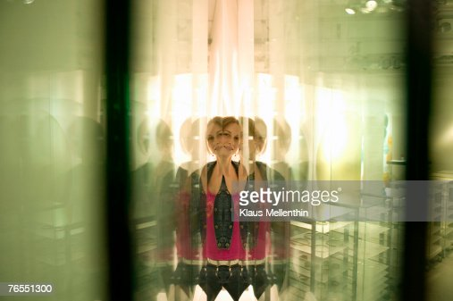 Teenage girl (16-17) reflecting in glass panes