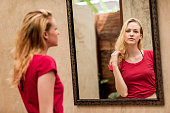 Young woman reflecting in mirror