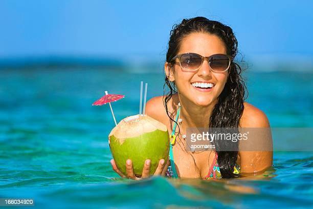 Junge Frau erfrischend in einem tropischen Strand mit Kokos-drink