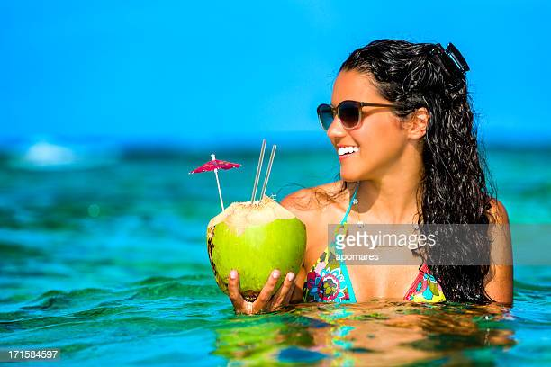 Young woman refreshing in a tropical beach with coconut drink