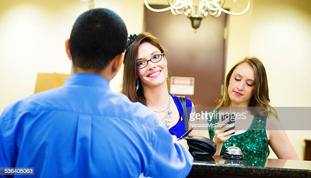 Junge Frau, die sich im hotel, während Freund Texte in mobile