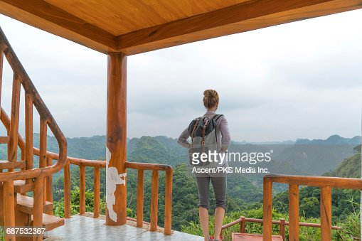 Young woman relaxes on deck, enjoys jungle view
