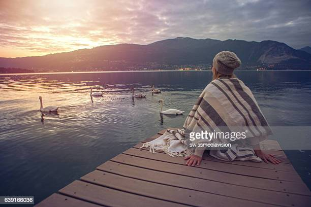 Young woman relaxes on lake pier