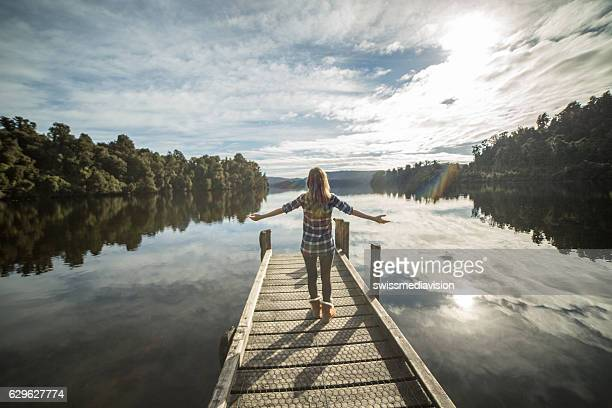 Young woman relaxes on lake pier, stands arms outstretched