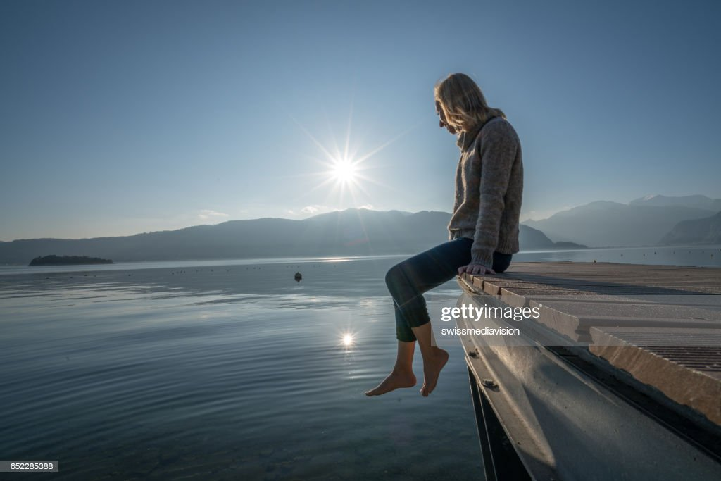 Young woman relaxes on lake pier, watches sunset : Foto stock