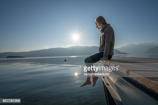 Young woman relaxes on lake pier, watches sunset : Bildbanksbilder