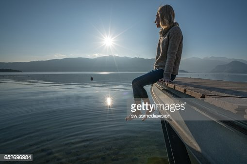 Young woman relaxes on lake pier, watches sunset : Photo