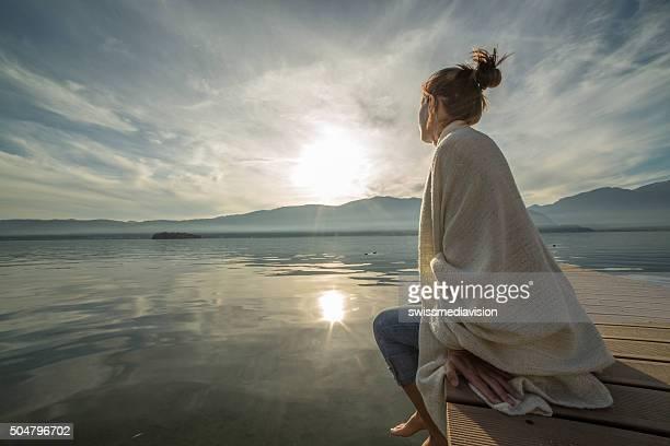 Jovem mulher relaxar no lago cais com cobertor, relógios pôr do sol