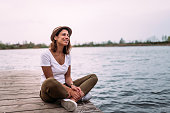 Young woman relaxes on the edge of a wooden jetty.