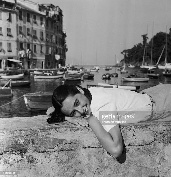 A young woman relaxes on the harbour wall in Portofino Italy 1951 Original publication Picture Post 5599 Portofino unpub