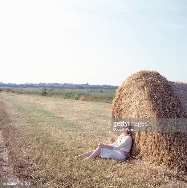 Young woman relaxing against hay bale, side view