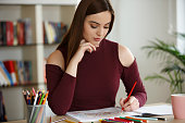 young woman relaxing at home coloring