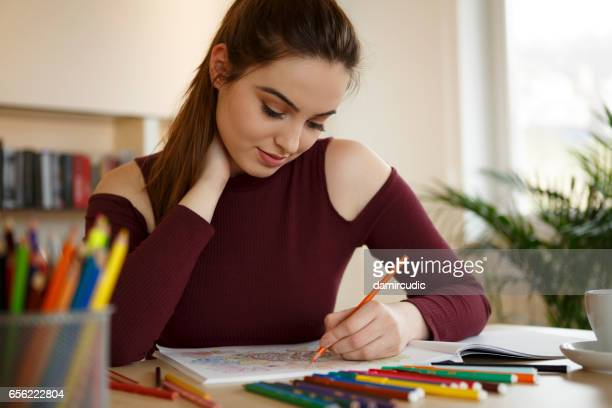 Young woman relaxing at home by coloring book