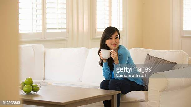 Young woman relaxing at home with a cup of tea,