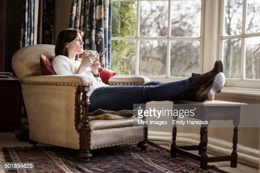A Young Woman Relaxing At Home With Her Feet Up Having A