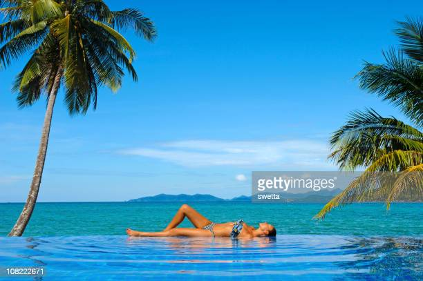 Young woman relaxing at pool on a tropical beach holiday