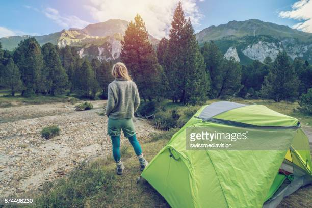 Young woman relaxing beside tent at sunset