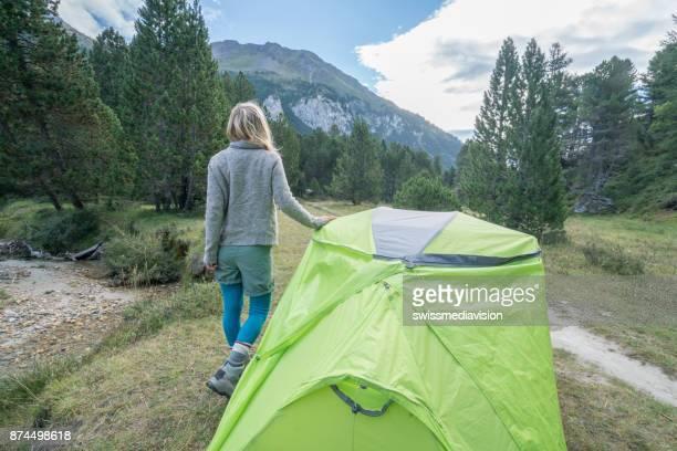 Jeune femme reposante à côté de la tente au coucher du soleil