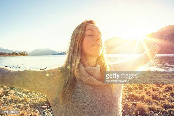 Young woman relaxing by the lake, mountain fresh air