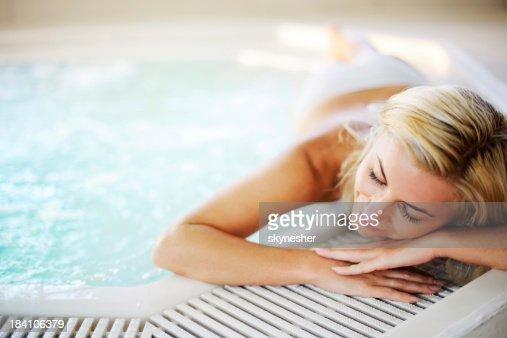 若い女性は、プールのそばでリラックス。