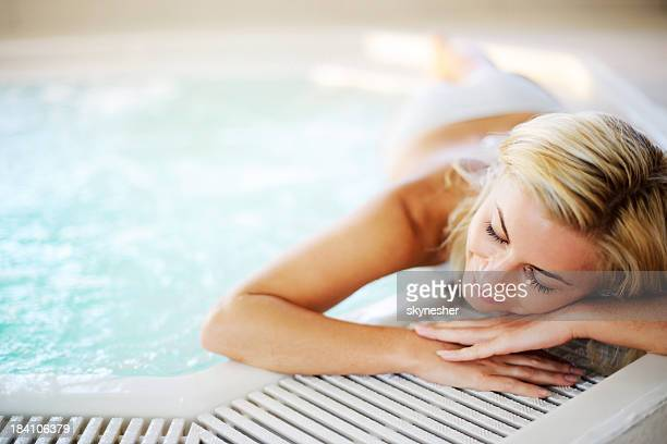 Young woman relaxing by the swimming pool.