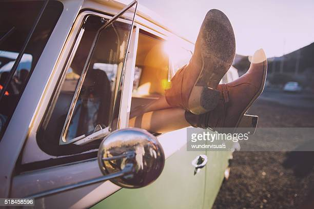 Young woman relaxing during a road trip with vintage van