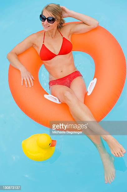 Young woman relaxing in a floating tire in a pool