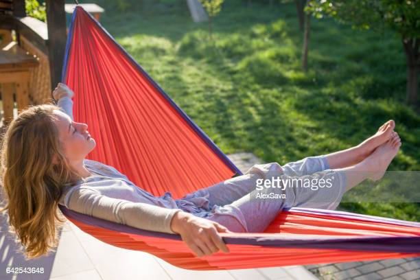 Young woman relaxing in a hammock on a sunny morning