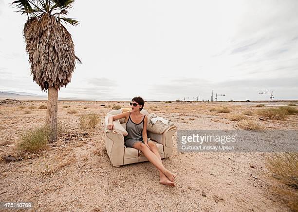 Young woman relaxing in armchair in desert