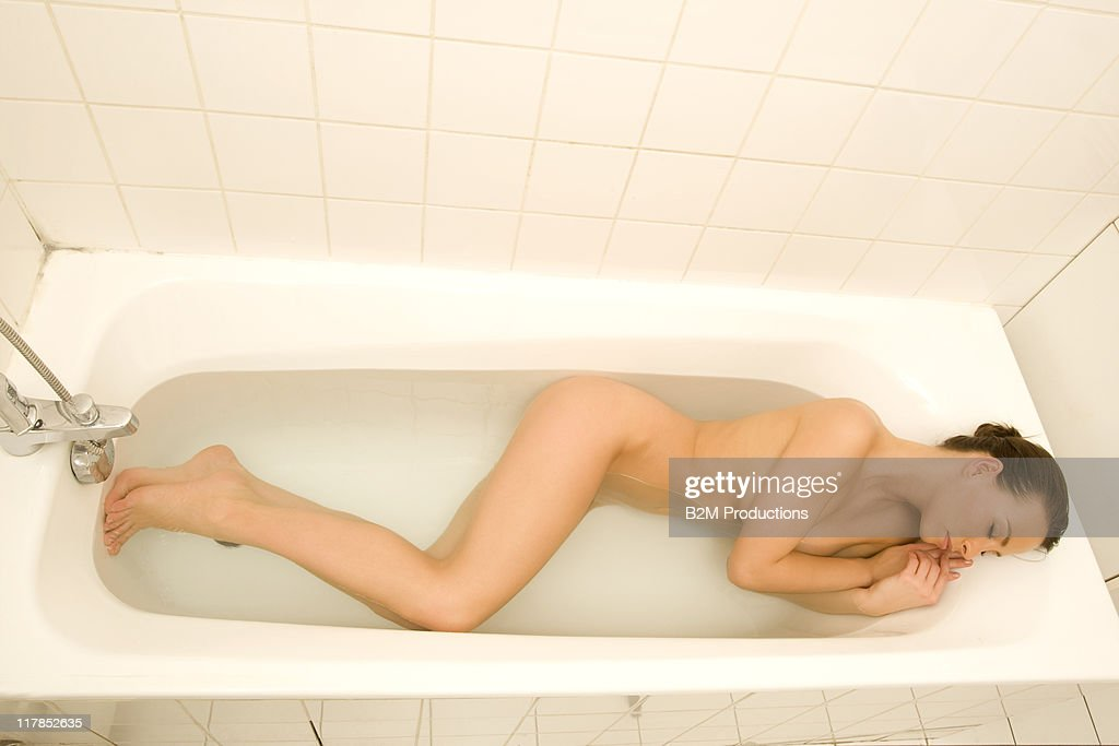 Young woman relaxing in bathtub, eyes closed : Stock Photo
