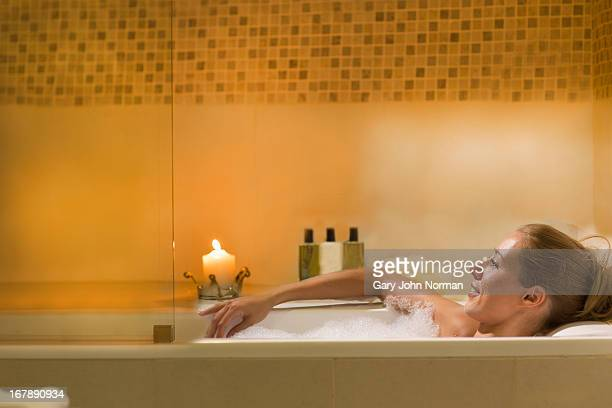 young woman relaxing in bubbly bath