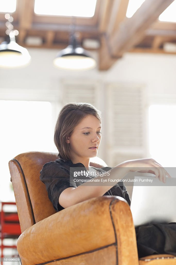 Young woman relaxing in chair using digital tablet : Stock Photo