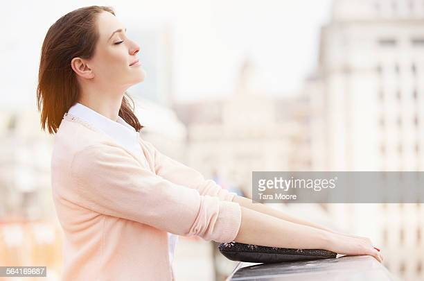 Young woman relaxing in city with eyes closed