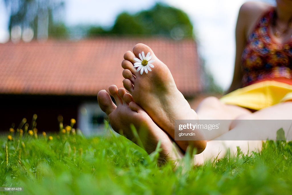Young Woman Relaxing in Grass with Flower Between Toes : Stock Photo