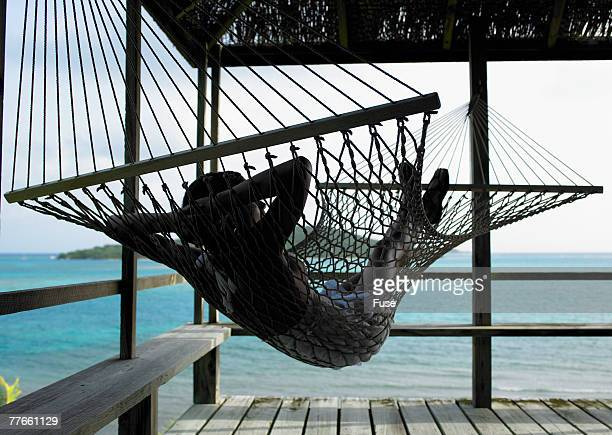Young Woman Relaxing in Hammock at Beach House