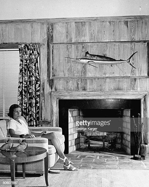 A young woman relaxing in her living room where there is a stuffed tuna mounted on the wall