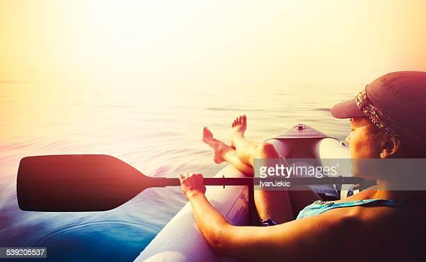 Junge Frau Entspannung in einem Kajak auf dem Meer bei Sonnenuntergang
