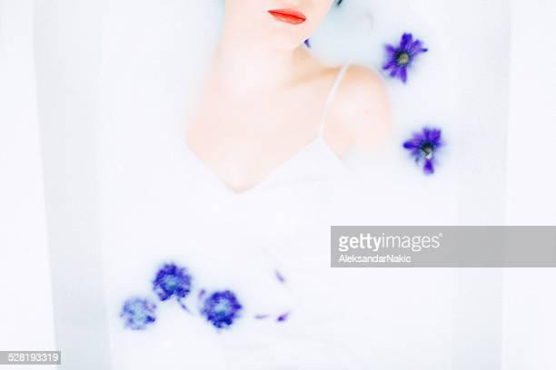 Jeune femme de détente dans le bain au lait