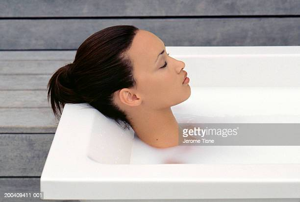 Young woman relaxing in milk bath, side view, elevated view