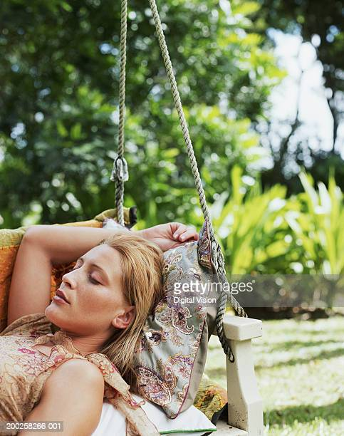 Young woman relaxing in swing chair, eyes closed, outdoors, close-up