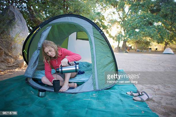 Young woman relaxing in tent pouring a cup of coffee, Van Zyl???????s Pass area, Kaokoland, Namibia