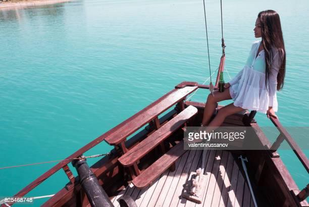 Jonge vrouw ontspannen op een boot en bier drinken