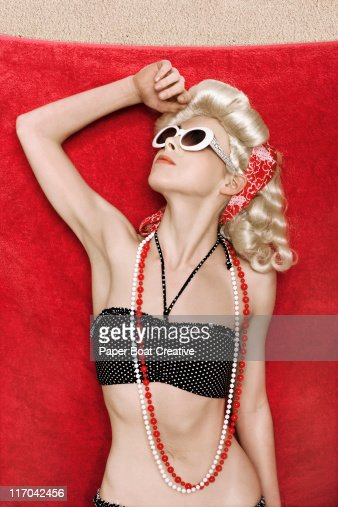 Young woman relaxing on a red towel : Stock Photo